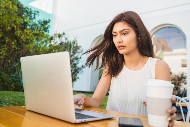 Портрет молодой латинской женщины, использующей свой ноутбук, сидя в кафе. концепция технологии и образа жизни.