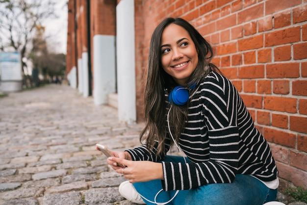 ヘッドフォンを持ち、通りで彼女の携帯電話を使用して若いラテン女性の肖像画。