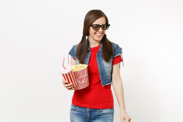 흰색 배경에 격리된 팝콘 양동이와 플라스틱 컵의 소다 또는 콜라를 들고 영화를 보고 있는 3d 안경을 쓴 젊은 웃고 있는 매력적인 여성의 초상화. 영화 개념의 감정.