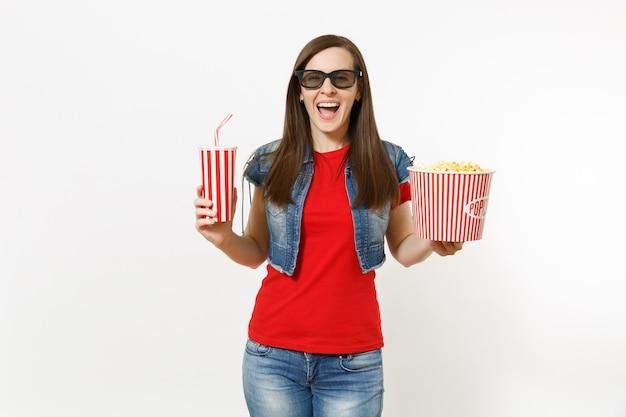 흰색 배경에 격리된 팝콘 양동이와 플라스틱 컵의 소다 또는 콜라를 들고 영화를 보고 있는 3d 아이맥스 안경을 쓴 젊은 웃고 있는 매력적인 여성의 초상화. 영화 개념의 감정.