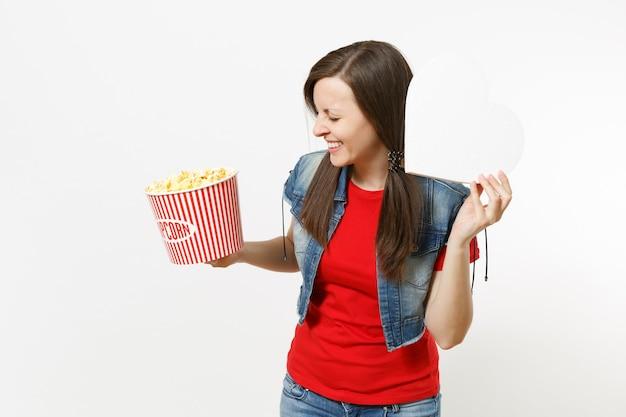 흰색 배경에 격리된 복사 공간이 있는 팝콘과 흰색 하트 양동이를 들고 영화를 보고 있는 캐주얼한 옷을 입은 젊은 웃고 있는 아름다운 여성의 초상화. 영화 개념의 감정.