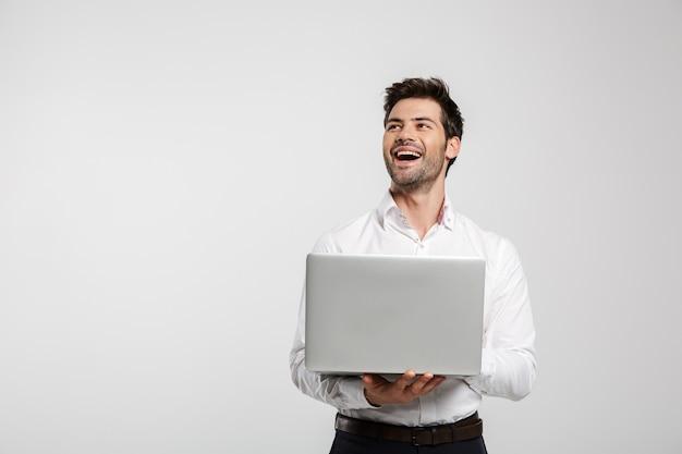 Портрет молодого смеющегося бизнесмена, держащего и использующего ноутбук, изолированного на белом