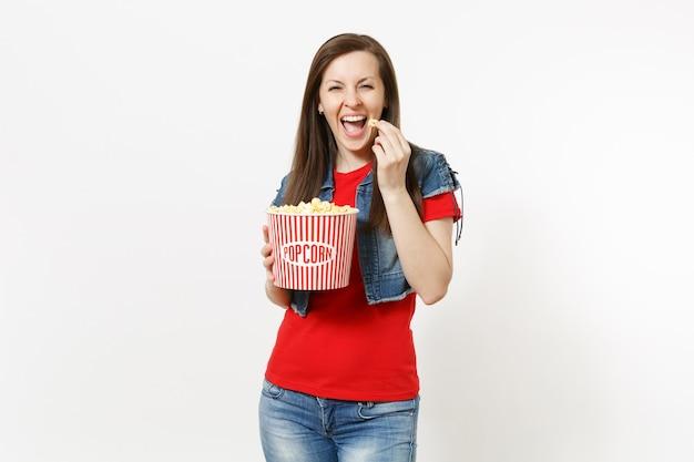흰색 배경에 격리된 양동이에서 팝콘을 들고 먹는 캐주얼 옷을 입고 영화를 보고 웃고 있는 젊고 아름다운 브루네트 여성의 초상화. 영화 개념의 감정.
