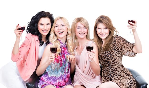 Портрет молодых смеющихся счастливых женщин, сидящих на диване с бокалами вина - изолированные