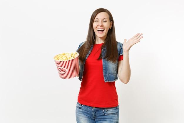 캐주얼한 옷을 입고 영화를 보고, 팝콘 양동이를 들고 흰색 배경에 격리된 손을 펼치고 있는 젊은 웃고 있는 아름다운 여성의 초상화. 영화 개념의 감정.