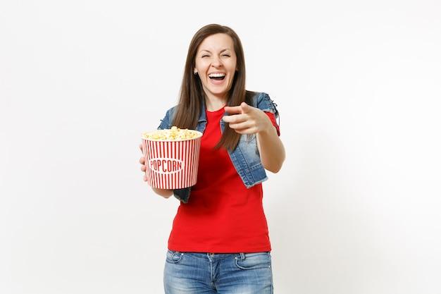 캐주얼한 옷을 입고 영화를 보고 웃고 있는 젊은 여성의 초상화, 팝콘 양동이를 들고 흰색 배경에 격리된 카메라에 검지 손가락을 가리킵니다. 영화 개념의 감정.