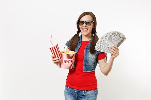 3d 안경을 쓴 웃고 있는 젊은 여성의 초상화, 팝콘 양동이, 소다 또는 콜라 한 컵, 달러 묶음, 흰색 배경에 격리된 현금 돈을 들고 영화를 보고 있습니다. 영화 속 감정.