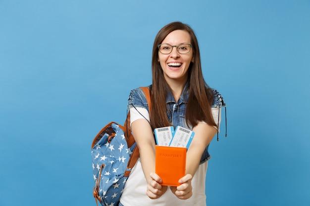 Портрет молодого смеющегося студента женщины в очках с рюкзаком, держащим билеты на посадочный талон паспорта, изолированные на синем фоне. обучение в вузе за рубежом. концепция полета авиаперелета.