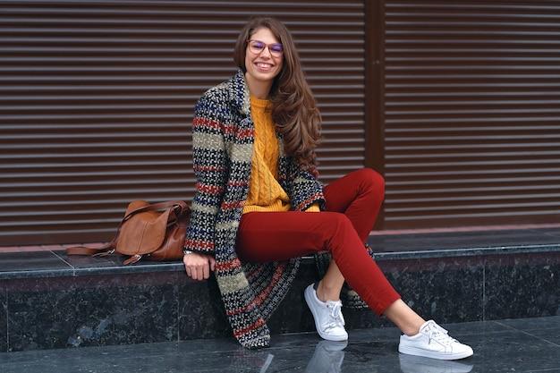 ヨーロッパの街の通りでポーズをとって、スタイリッシュなコート、赤いズボン、オレンジ色のセーター、白いスニーカー、茶色の革のバッグを身に着けている若い、笑っている女性の肖像画。コピースペース