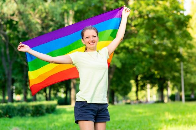 젊은 레즈비언 행복하고 자랑스러운 여성의 초상화, 아름다운 소녀는 자연 배경에서 여름 화창한 날에 무지개 lgbt 색 게이 깃발을 흔들고 있습니다. lgbt 커뮤니티, 동성애 평등 개념