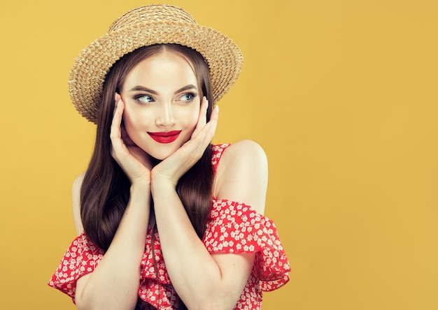 明るい赤い夏のガウンと麦わら帽子に身を包んだ若い、長い髪のモデルの肖像画。唇に優しい笑顔と心地よい表情、顔に赤い口紅をあしらった明るいメイク、化粧品
