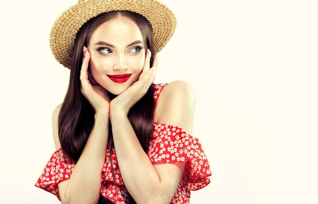 빛, 빨간 여름 가운과 밀짚 모자를 입은 젊은, 긴 머리 모델의 초상화. 입술에 은은한 미소로 기분 좋은 표정, 얼굴에 빨간 립스틱을 바른 화사한 메이크업 화장품.