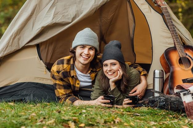 観光客の若い愛するカップルの肖像画は森の中でデートをしています