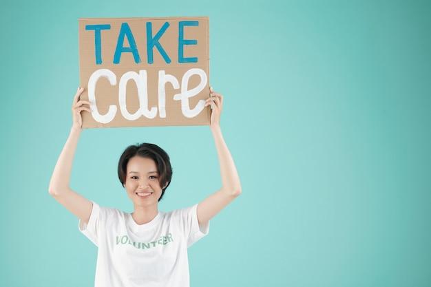 Портрет молодой милой азиатской женщины, держащей плакат с надписью заботиться над головой hr и улыбающейся в камеру