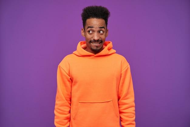 若い素敵なひげを生やした暗い肌の巻き毛のブルネットの男の肖像画は、紫色の上に立っている間、手を下に置いて、混乱したしかめっ面で積極的に脇を見て