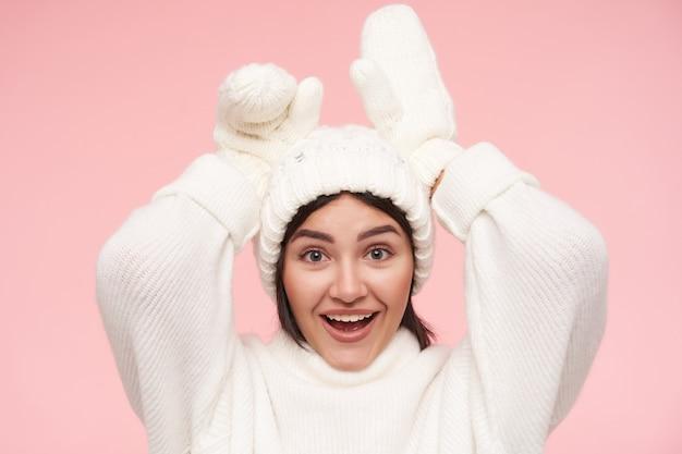 Портрет молодой милой брюнетки с естественным макияжем, счастливо улыбающейся, обманывая и имитируя уши с поднятыми руками, стоя над розовой стеной