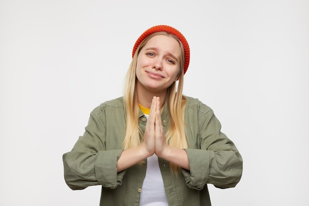 Портрет молодой милой длинноволосой блондинки, держащей поднятые ладони вместе, умоляющей о чем-то и мрачно выглядящей, позирующей на синем