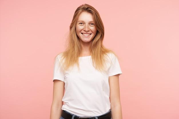 ピンクの背景の上に立って、広い笑顔で元気にカメラに微笑んでいる間、彼女の手を下に保つ若い素敵な長い髪の赤毛の女性の肖像画