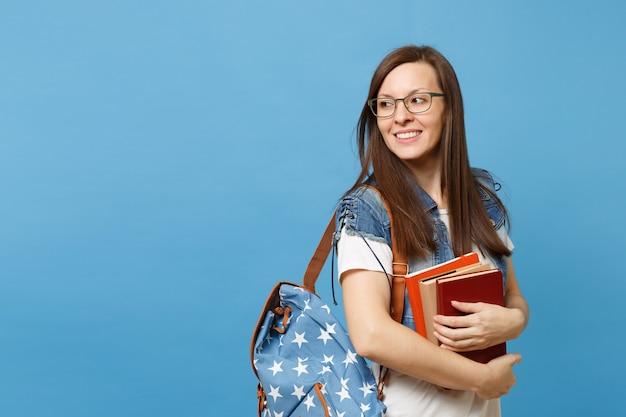 目をそらしているバックパックとメガネで若い素敵な笑顔の女性学生の肖像画は、青い背景で隔離の学習の準備ができて教科書を保持します。高校大学カレッジコンセプトの教育。
