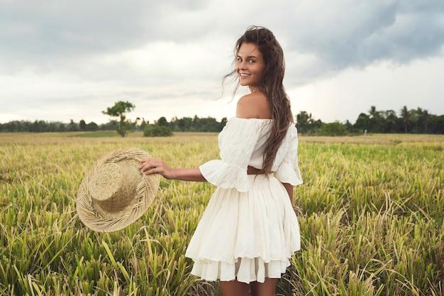 Портрет молодой прекрасной женщины, держащей соломенную шляпу на рисовом поле