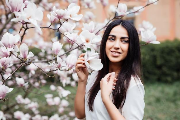 봄 꽃 목련 나무에 젊은 사랑스러운 여자의 초상화