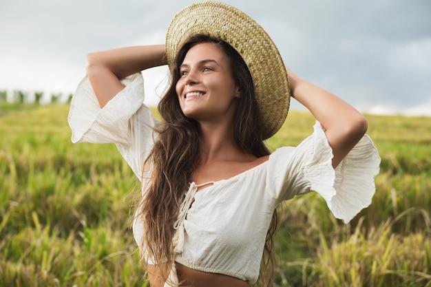 Портрет молодой прекрасной женщины в соломенной шляпе на рисовом поле