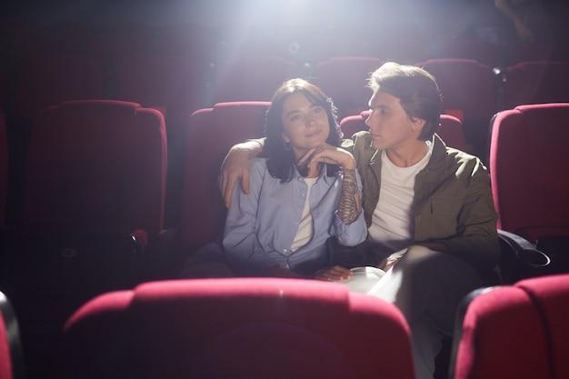Портрет молодой влюбленной пары в кино, смотрящей фильм, наслаждаясь свиданием, мужчина смотрит на подругу с любовью и обнимает ее, копирует пространство