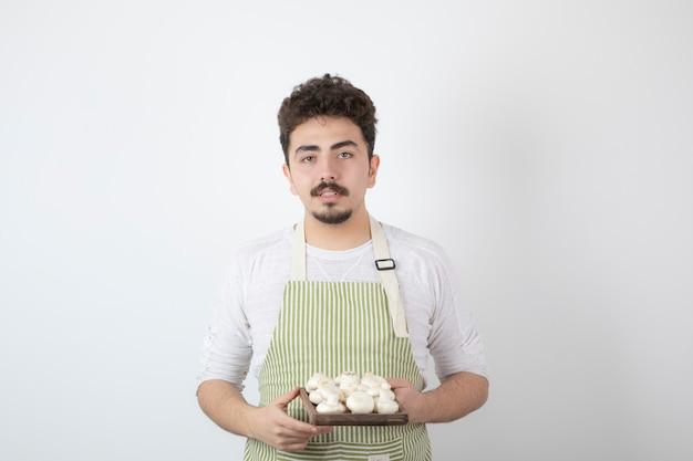 Портрет молодого мужского повара, держащего сырые грибы на белом