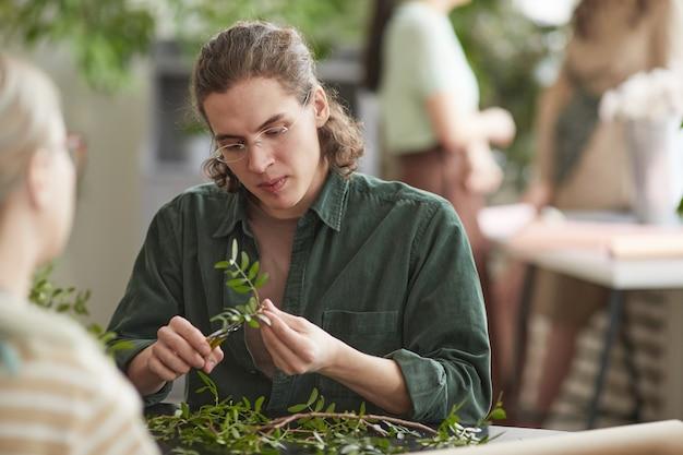 装飾、コピースペースのための花の組成物を作成しながら緑の植物を切る若い男性の花屋の肖像画