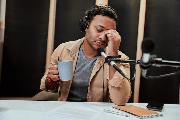 커피를 마시는 동안 피곤해 보이는 헤드폰을 끼고 있는 젊은 남성 라디오 진행자의 초상화