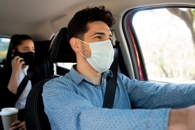 뒷 좌석에서 비즈니스 여자 승객과 젊은 남성 택시 운전사의 초상화. 새로운 정상적인 라이프 스타일 컨셉