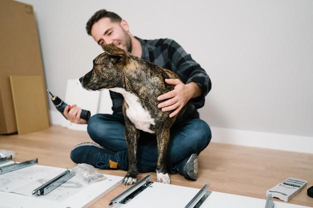 家具を組み立てる若い男と彼の犬の肖像画