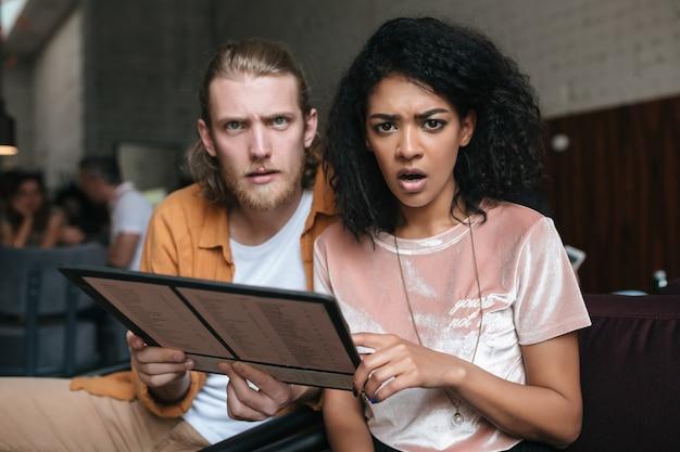Портрет молодого мужчины и женщины, сидящей в ресторане с меню в руках