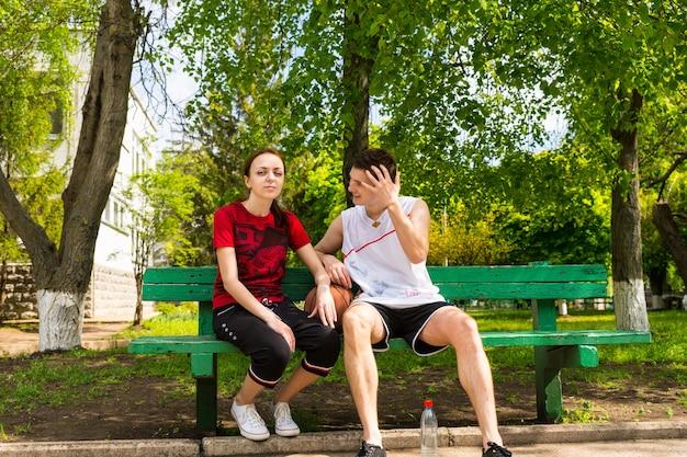 녹색 공원 벤치에 앉아 농구를 하고 경기 후 휴식을 취하는 운동복을 입은 젊은 남자와 여자의 초상화