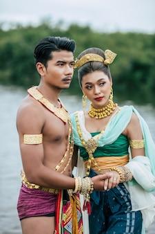 タイの自然の中でポーズをとる伝統的な衣装を着た若い男性と女性の肖像画