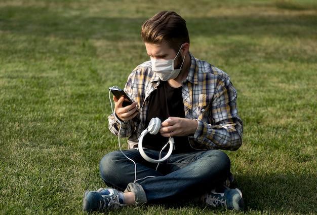 屋外で携帯電話を閲覧する若い男の肖像