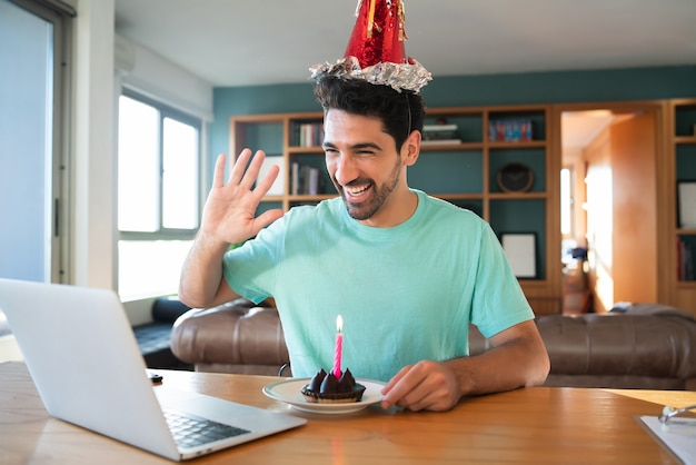 노트북과 케이크와 함께 가정에서 화상 통화에 생일을 축하하는 젊은 남자의 초상화. 새로운 정상적인 라이프 스타일 개념.