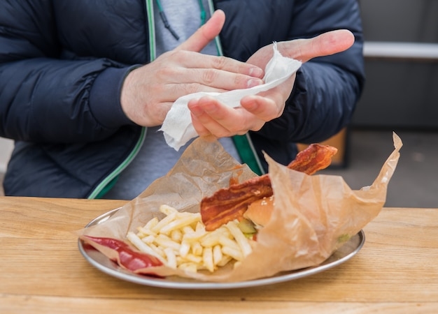 Портрет молодого человека, протирающего руки влажной салфеткой перед едой гамбургера