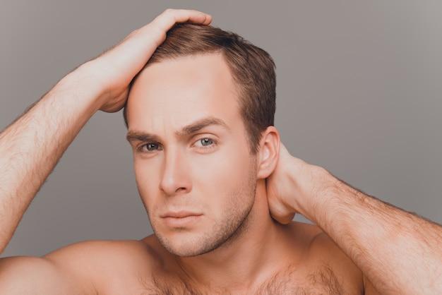 Портрет молодого человека, расчесывающего волосы пальцами