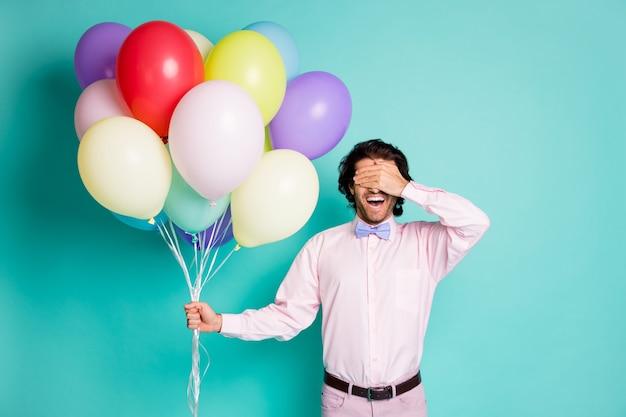젊은 남자의 초상화는 정장을 입은 눈을 덮고 화려한 풍선을 들고 청록색 배경에서 격리된 파티를 놀라게 합니다.
