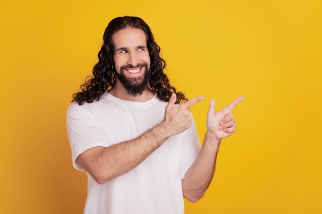 若い男の直接人差し指の空白のスペースの肖像画は、黄色の背景に笑顔を輝かせてサイドアップを見てください