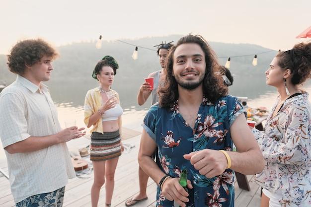 Портрет молодого человека, пьющего пиво и улыбающегося в камеру, развлекаясь на вечеринке