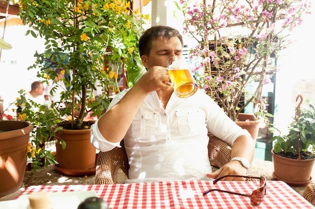 레스토랑 여름 테라스에서 더운 날에 맥주를 마시는 젊은 남자의 초상화
