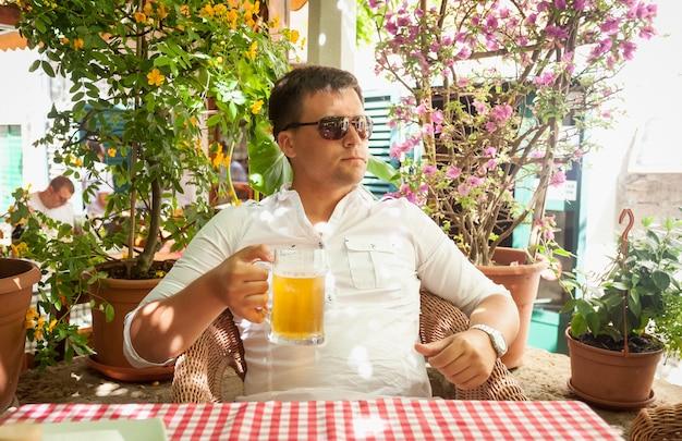 레스토랑에서 맥주를 마시는 젊은 남자의 초상화