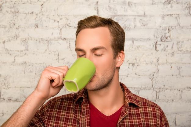 Портрет молодого человека, пьющего чай на фоне кирпичной стены