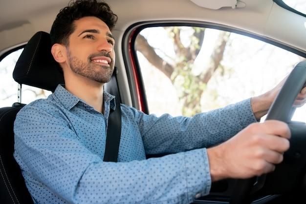 출근 길에 그의 차를 운전하는 젊은 남자의 초상화. 전송 개념.
