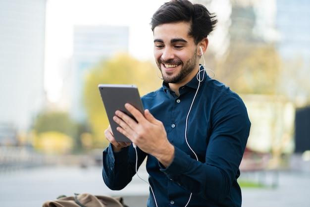 屋外のベンチに座っている間にデジタルタブレットでビデオ通話をしている若い男の肖像画