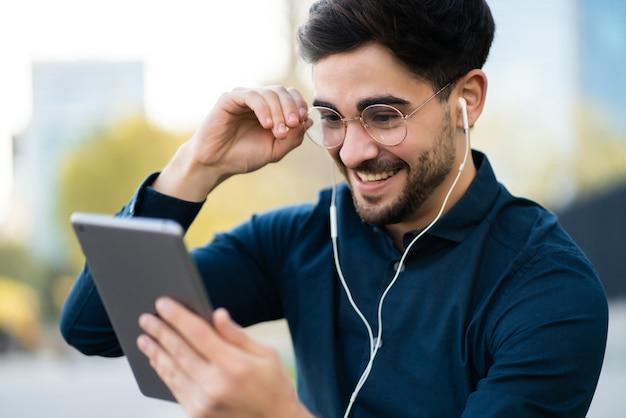 야외 벤치에 서있는 동안 디지털 태블릿에 화상 통화를하는 젊은 남자의 초상화