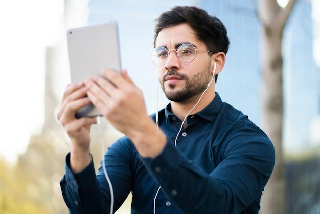 屋外に立っているときにデジタルタブレットでビデオ通話をしている若い男の肖像画。アーバンコンセプト。
