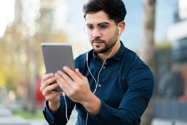 屋外に立っているときにデジタルタブレットでビデオ通話をしている若い男の肖像画